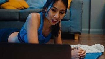 ung asiatisk dam i sportkläder övningar som tränar och använder bärbar dator för att titta på yoga video tutorial hemma kväll. avlägsen utbildning med personlig tränare, social distans, online utbildningskoncept. foto