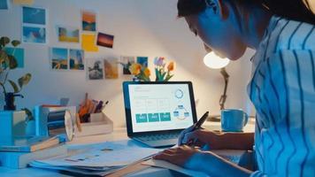 unga asiatiska affärskvinna frilans fokus på bärbar dator skriva kalkylblad finans diagram diagram marknadsplan i bärbar dator och surfplatta hemma natten. flicka student lära sig online, arbeta hemifrån koncept. foto