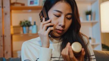 sjuk ung asiatisk kvinna hålla medicin sitta i soffan använda smart telefon för att rådgöra med läkare hemma natten. tjej tar medicin efter läkarorder, karantän hemma, socialt avstånd coronavirus -koncept. foto