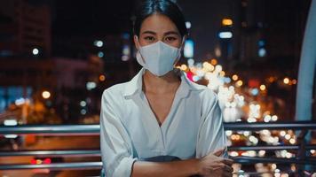 framgångsrik ung asiatisk affärskvinna i mode kontorkläder bär medicinsk ansiktsmask leende och tittar på kameran medan den är fristående ensam utomhus i den urbana moderna stadskvällen. business on go -koncept. foto