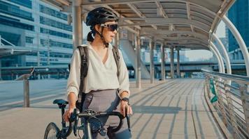 asiatisk dam affärskvinna bära solglasögon gå till jobbet på kontorspromenad och le titta runt håll cykelställ runt byggnaden på en stadsgata. cykelpendling, pendling på cykel, affärspendelkoncept. foto