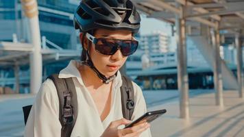 glad asiatisk affärskvinna med ryggsäck använder smart telefon i stadens stativ på gatan med cykel går till jobbet på kontoret. sportflicka använder sin telefon för att jobba. pendla till jobbet, affärspendlare i staden. foto
