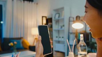 ung asiatisk dam använder smart telefon med tom svart skärm hämmar display för reklamtext medan smart arbetar hemifrån i vardagsrummet på natten. chroma key -teknik, marknadsföringskoncept. foto
