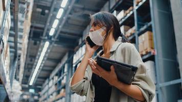 ung asiatisk affärskvinna online säljare bär ansiktsmask pratar bekräftar beställning från kund på telefon håll tablettställ i detaljhandeln köpcentrum. distribution, logistik, paket redo för leverans. foto