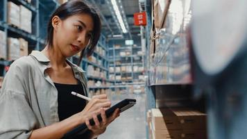 attraktiv ung asiatisk affärskvinnechef som söker varor med hjälp av digital surfplatta som kontrollerar lagernivåer som står i detaljhandelscentret. distribution, logistik, paket redo för leverans. foto