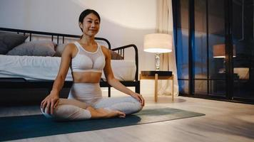 ung asiatisk dam i sportkläder som gör yogaövning som tränar i vardagsrummet hemma på natten. sport och rekreationsaktivitet, social distansering, karantän för att förebygga corona -virus. foto