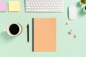 kreativt plattläggningsfoto av skrivbordet på arbetsytan. ovanifrån kontorsbord med tangentbord, mus och svart mockup anteckningsbok på pastellgrön bakgrund. ovanifrån håna med kopia utrymme fotografering. foto