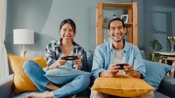lyckligt asien ungt par man och kvinna sitter på soffan använder joystick controller spela videospel tillbringa rolig tid tillsammans i vardagsrummet. asiatiska gift par familj livsstil, par stanna hemma koncept. foto