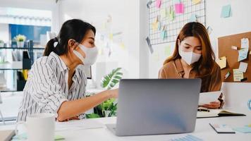 asiatiska affärsmän som använder datorpresentation möter brainstorming av idéer om nya projektkollegor och bär skyddande ansiktsmask tillbaka i ett nytt normalt kontor. livsstil och arbete efter coronaviruset. foto