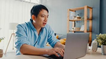 frilans asien kille fritidskläder med bärbar dator online i vardagsrummet på hemmakontoret. jobba hemifrån, arbeta på distans, distansutbildning, social distansering, karantän för förebyggande av corona -virus. foto