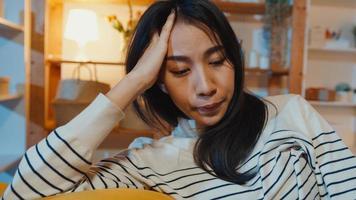 eftertänksam asiatisk dam som lider av sömnlöshet sitta i soffan i vardagsrummet hemma på natten med att känna sig ensam, ledsen deprimerad tonåring tillbringa tid ensam stanna hemma, social distans, coronavirus -karantän. foto