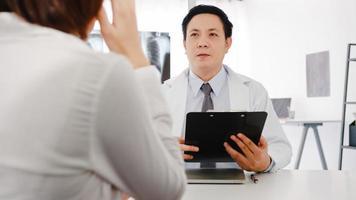 allvarlig asiatisk manlig läkare i vit medicinsk uniform med urklipp levererar bra nyheter prata diskutera resultat eller symptom med kvinnlig patient som sitter vid skrivbordet på vårdkliniken eller sjukhuskontoret. foto