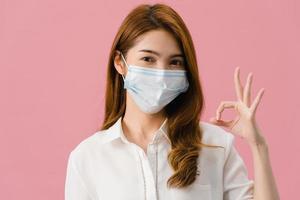 ung asiatisk tjej bär medicinsk ansiktsmask gestikulerar skylt med klädd i vardaglig trasa och titta på kameran isolerad på rosa bakgrund. självisolering, social distansering, karantän för corona-virus. foto