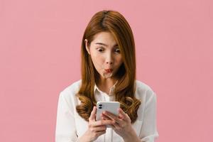 ung asiatisk dam med telefon med positivt uttryck, ler brett, klädd i vardagskläder som känner lycka och står isolerad på rosa bakgrund. glad förtjusande glad kvinna jublar över framgång. foto