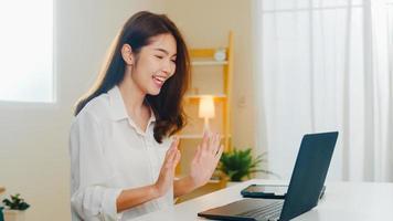 ung asiatisk affärskvinna som använder videosamtal med laptop och pratar med par medan de arbetar hemifrån i vardagsrummet. självisolering, social distansering, karantän för coronavirus i nästa normala koncept. foto