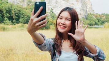glad ung resenär asiatisk dam med ryggsäck selfie vid fjällsjön. koreansk tjej glad att använda mobiltelefon som tar selfie njuta av semester på vandring äventyr. livsstilsresor och koppla av koncept. foto