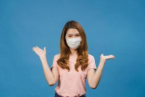 ung asiatisk tjej som bär medicinsk ansiktsmask som visar fredstecken, uppmuntra med klädd i vardaglig trasa och titta på kameran isolerad på blå bakgrund. social distansering, karantän för corona. foto