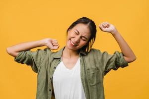 ung asiatisk dam med positivt uttryck, glad och spännande, klädd i avslappnad trasa över gul bakgrund med tomt utrymme. glad förtjusande glad kvinna jublar över framgång. ansiktsuttryck koncept. foto