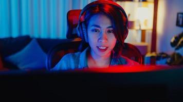 närbild ansikte glad asien professionell tjej spelare bära hörlurar tävling spela videospel neonljus dator i vardagsrummet hemma. esport -strömmande spel online, hemmakarantänaktivitetskoncept. foto