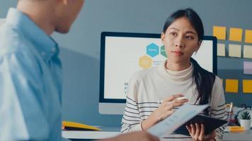 glada unga asiatiska affärsmän och affärskvinnor möter brainstorming några nya idéer om projekt till sin partner som arbetar tillsammans planerar framgångsstrategi njuter av lagarbete i små moderna hemmakontor. foto