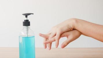 asiatisk kvinna som använder alkoholgel handsprit tvättar hand för att skydda coronaviruset. kvinnlig push -alkoholflaska för att rengöra handen för hygien när social distansering stannar hemma och självkarantänstid. foto