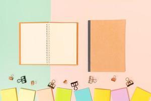 kreativt plattläggningsfoto av skrivbordet på arbetsytan. ovanifrån kontorsbord med självhäftande lapp och öppen mockup svart anteckningsbok på pastellgrön rosa färgbakgrund. ovanifrån håna med kopia utrymme fotografering. foto