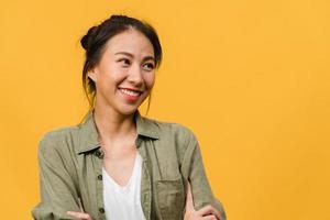 porträtt av ung asiatisk dam med positivt uttryck, korsade armen, le stort, klädd i avslappnad trasa över gul bakgrund. glad förtjusande glad kvinna jublar över framgång. ansiktsuttryck koncept. foto