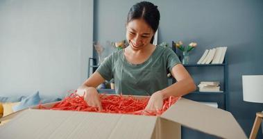 glad vacker asiatisk dam, unboxing kartong leveranspaket från online -marknadsplatsen i vardagsrummet hemma. nöjd shoppare i internetförpackning av varor, onlineshopping och leveranskoncept. foto