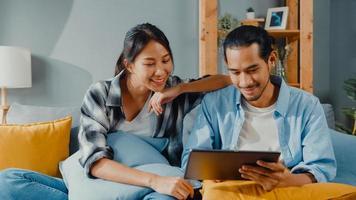 lyckliga asiatiska unga attraktiva par man och kvinna sitter på soffan använda surfplatta shopping online möbler dekorera hem i vardagsrummet på nya hus. unga gifta flyttar hem shopper online koncept. foto
