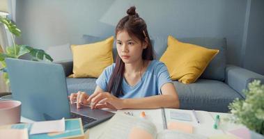 ung Asien flicka tonåring med tillfällig användning bärbar dator lära sig online skriva föreläsning anteckningsbok för sista testet i vardagsrummet hemma. isolera utbildning online e-learning coronavirus-pandemikoncept. foto