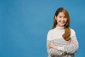 porträtt av ung asiatisk dam med positivt uttryck, korsade armar, le brett, klädd i vardagskläder och titta på kameran över blå bakgrund. glad förtjusande glad kvinna jublar över framgång. foto