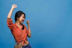 ung asiatisk dam med positivt uttryck, glad och spännande, klädd i vardagsduk över blå bakgrund med tomt utrymme. glad förtjusande glad kvinna jublar över framgång. ansiktsuttryck koncept. foto