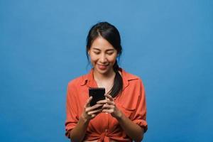 ung asiatisk dam som använder telefon med positivt uttryck, ler brett, klädd i vardagskläder som känner lycka och står isolerad på blå bakgrund. glad förtjusande glad kvinna jublar över framgång. foto
