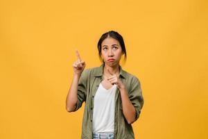 ung asiatisk dam visar något fantastiskt på tomt utrymme med negativt uttryck, upphetsad skrik, gråter känslomässigt arg i vardagskläder isolerad över gul bakgrund. ansiktsuttryck koncept. foto