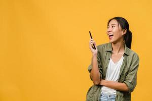 ung asiatisk dam med telefon med positivt uttryck, ler brett, klädd i vardagskläder som känner lycka och står isolerad på gul bakgrund. glad förtjusande glad kvinna jublar över framgång. foto