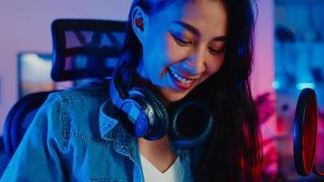 glad asiatisk tjejbloggare spela synthesizer -tangentbord bär hörlurar och spela in musik med ljudmixer på bärbar dator i vardagsrummet hemstudio på natten. musikinnehållsskapare, handledning, sändningskoncept. foto