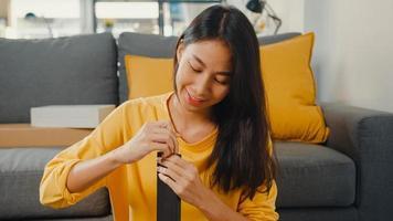 glad asiatisk ung kvinna packar upp lådan och läser instruktionerna för att montera nya möbler dekorera husbygga bord med kartonglåda i vardagsrummet hemma. foto
