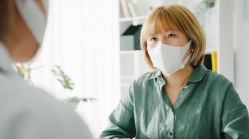 ung asiatisk damläkare bär skyddsmask med urklipp levererar bra nyheter prata diskutera resultat eller symtom med tjejpatient på sjukhuskontoret. livsstil ny normal efter corona -virus. foto