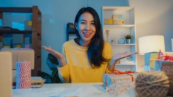glad ung asiatisk affärskvinna som tittar på kamerasäljning introducerar produkt till klientvideo livestreaming på nätbutiksmarknaden på natten. småföretagare, online marknadsföringskoncept. foto
