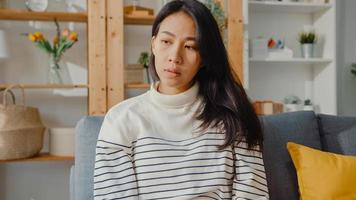 tankeväckande asiatisk dam sitter och omfamnar knän i soffan i vardagsrummet hemma och tittar ut utanför med ensam känsla, ledsen deprimerad tonåring tillbringar tid ensam stannar hemma, social distans, coronavirus -karantän. foto