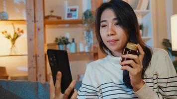 sjuk ung asiatisk dam hålla medicin sitta i soffan videosamtal med telefon konsultera läkare hemma natten. flicka ta medicin efter läkares order, karantän hemma, social distans corona virus. foto