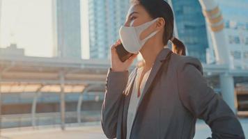 ung asiatisk affärskvinna i modekontor klär sig i medicinsk ansiktsmask prata via telefon medan hon går ensam utomhus i stad. företag på gång, social distansering för att förhindra spridning av covid-19-konceptet. foto