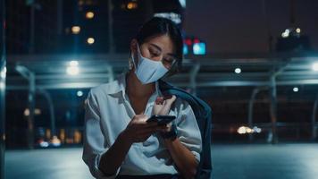 ung asiatisk affärskvinna i modekläder som bär ansiktsmask med hjälp av smarttelefon som skriver textmeddelande medan du står utomhus i stadens stad på natten. social distansering för att förhindra spridning av covid-19-konceptet. foto