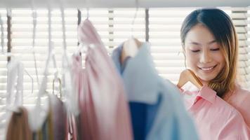 vacker attraktiv ung asiatisk dam som väljer sina modekläder i garderoben hemma eller i affären. tjej tänk vad man ska ha på sig en casual skjorta. hemmagarderob eller klädbutik omklädningsrum. foto