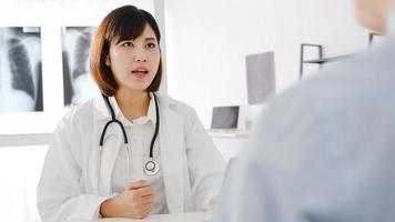 ung asiatisk kvinnlig läkare i vit medicinsk uniform som använder dator laptop levererar bra nyheter prata diskutera resultat eller symptom med manlig patient sitter vid skrivbordet på vårdkliniken eller sjukhuskontoret. foto