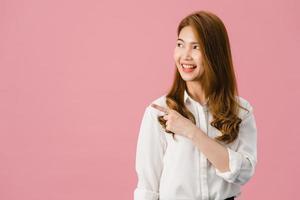 porträtt av ung asiatisk dam som ler med glatt uttryck, visar något fantastiskt på tomt utrymme i vardagskläder och står isolerat över rosa bakgrund. ansiktsuttryck koncept. foto