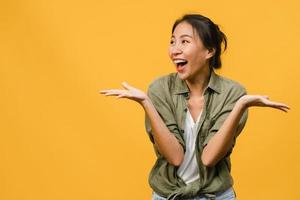 ung asiatisk dam känner lycka med positivt uttryck, glädjande överraskning funky, klädd i avslappnad trasa isolerad på gul bakgrund. glad förtjusande glad kvinna jublar över framgång. ansiktsuttryck. foto