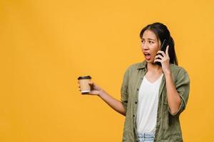 ung asiatisk dam pratar i telefon och håller kaffekoppen med negativt uttryck, upphetsad skrik, gråter känslomässigt arg i vardaglig trasa och står isolerad på gul bakgrund. ansiktsuttryck koncept. foto