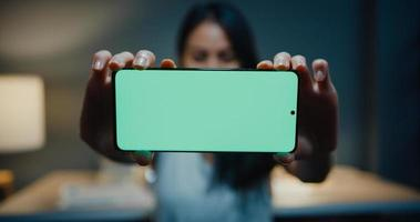 ung asiatisk tjej smart vardagskläder tittar på kameran, le, glad och visa mock-up skärm smartphone i modern hus natt. arbete hemifrån, social distans, chroma key mobiltelefon, surfning på internet. foto