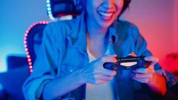 glad asien tjej spelare bär hörlurar och joystick kontroller prata med vän känner roligt och upphetsad med tävling online spel i neon vardagsrum hem studio på natten, hem karantän aktivitet. foto